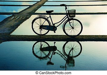 Bicycle refect on water surface at sunset - Bicycle put on...