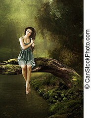 Forest idyll - The girl sits on a tree over the water in the...