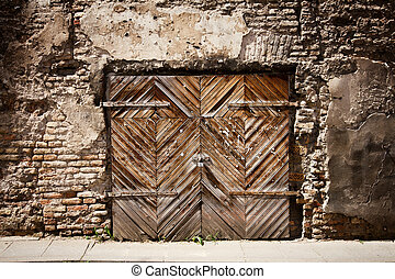 Old wooden gate in cracked brick wall