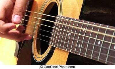 playing at guitar - close-up man hands playing at acoustic...