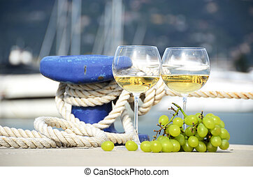 Pair of wineglasses and grapes against the yacht pier of La Spezia, Italy