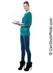 Teen browsing internet on her laptop