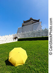 Yellow umbrella on green grass with blue sky