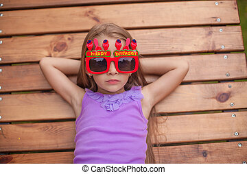 Adorable little girl in glasses with the words Happy Birthday outdoors