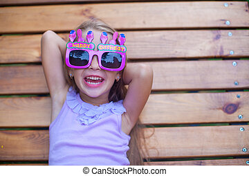 Adorable little girl in Happy Birthday glasses have fun outdoor