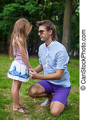 Young happy father talking with cute daughter in the park