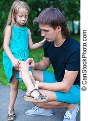 Young father pities his little daughter, who hurt her leg