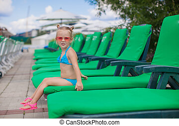 Little happy girl on the loungers by pool looking at camera
