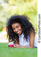 Smiling teenage black girl using a phone, lying down on the...