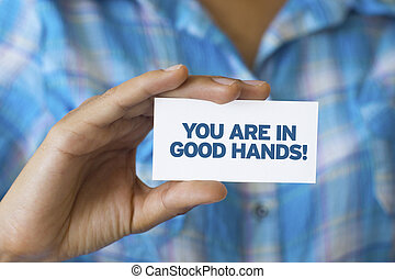 You are in Good hands - A person holding a white card with...