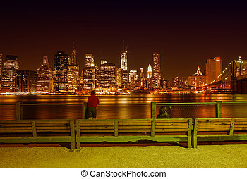 New York City at night in summer. View of Manhattan skyline from Brooklyn Bridge Park.