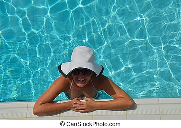 Happy woman in swimming pool - Happy smiling woman with hat...