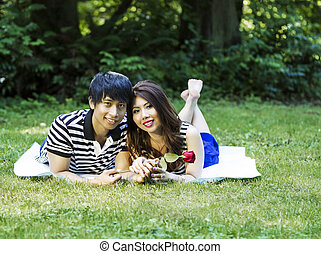 Young Adult Couple Lying on Blanket Outdoors