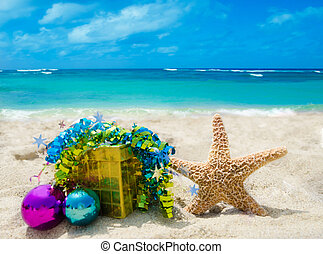 Starfish with gift box and Christmas balls on sandy beach in sunny day- holiday concept