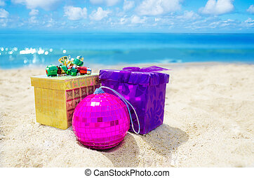 Two gift boxes Christmas ball on sandy beach in sunny day- holiday concept