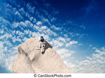 Young man climbing on a limestone wall with blue sky on the...