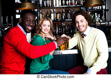 Three friends in bar enjoying beer - Three smiling young...