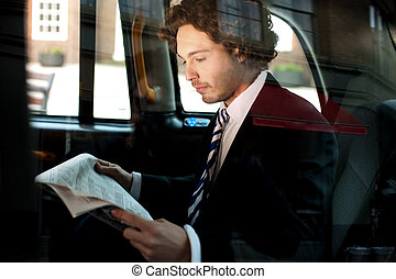 Man reading newspaper inside taxi cab - Businessman reading...
