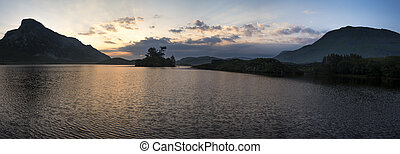 Panorama of beautiful sunrise reflected in calm Cregennen Lakes in Snowdonia National Park landscape