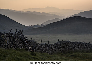 View along misty valley towards Snowdonia mountains - View...