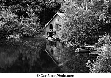 Black and white retro style picture of derelict boathouse and rowing boats landscape