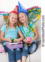 Cute twins unwrapping their birthday present sitting on a...