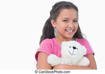 Little girl holding her teddy bear on white background