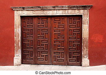 wooden ornament gate in red wall. mexican architecture