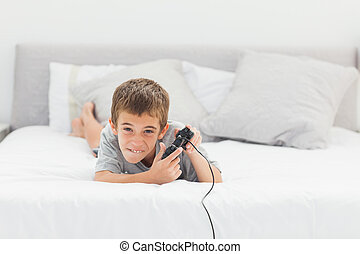 Little boy playing video games lying on bed