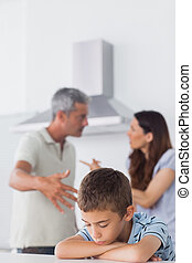 Couple having dispute in front of their sad son sitting in...
