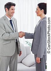 Happy colleagues shaking hands during meeting at office