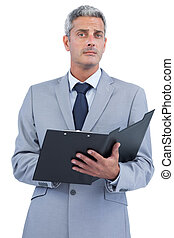 Self assured businessman with clipboard on white background