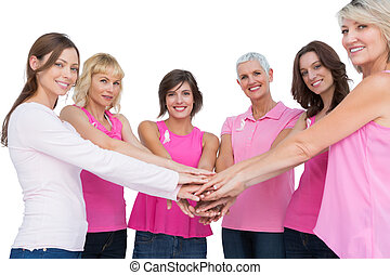 Cheerful women posing in circle holding hands looking at...