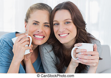 Smiling women holding their cup of coffee sitting on the...