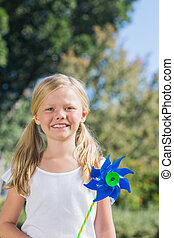 Cute blonde girl holding pinwheel smiling at camera