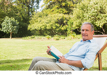 Happy mature man holding book and looking at camera in the...