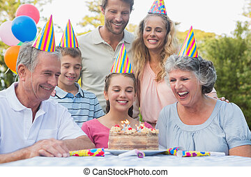 Cheerful extended family celebrating a birthday outside at...