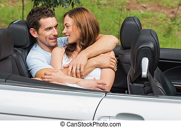 Couple in love cuddling in the backseat and chatting