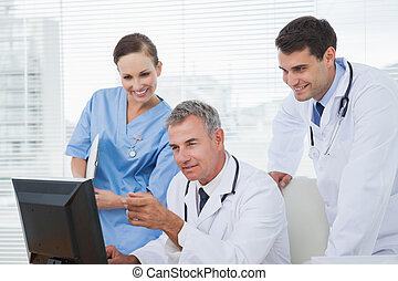 Doctors and surgeon working together on computer in bright...