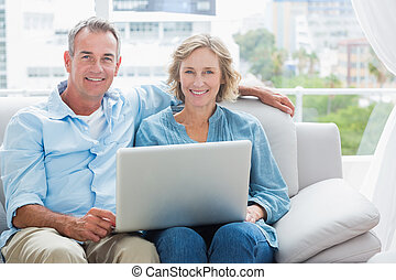 Happy couple relaxing on their couch using the laptop...