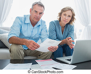 Worried couple paying their bills online with laptop looking at camera at home in the living room