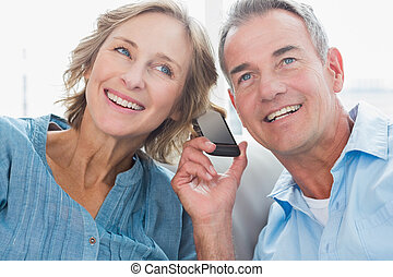 Happy couple listening to mobile phone together at home in...