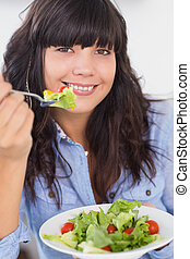 Smiling brunette having a salad for