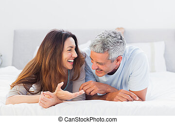 Cute couple lying on bed talking together at home