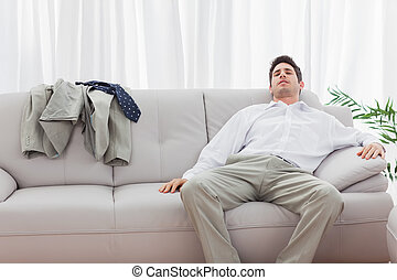 Tired businessman sitting back on sofa at home after long...