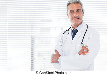 Smiling doctor crossing his arms in medical office