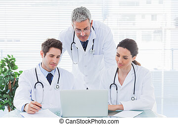 Team of concentrated doctors working together with their...