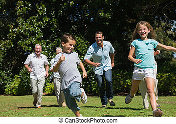 Happy multi generation family racing towards camera in a...