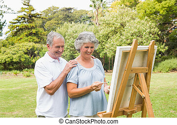 Cheerful retired woman painting on canvas with husband in...