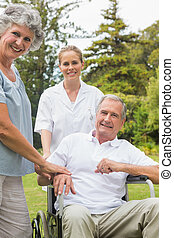 Happy man in a wheelchair with his nurse and wife